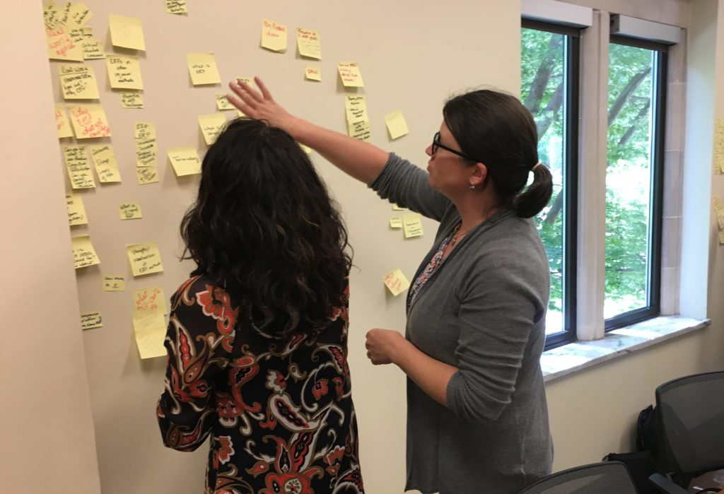 Two faculty members organizing a wall of post-it notes